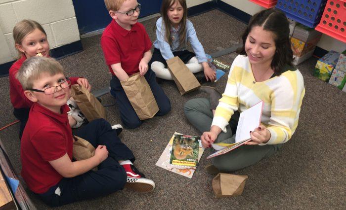The Vanguard School Teacher reads to hear kindergarten students sitting on the floor in a semi-circle