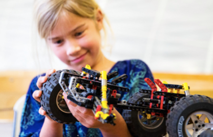Girl working on designing and building a Lego truck